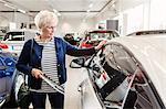 Senior woman admiring car in dealership store