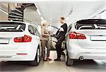 Full length of senior saleswoman talking to male customer at car dealership