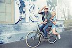 Portrait playful couple riding bicycle along urban graffiti wall