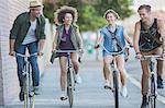 Friends riding bicycles on urban sidewalk