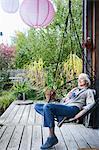 Mature woman relaxing in chair on veranda