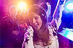 Young woman wearing headphones and dancing in nightclub
