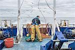 Fisherman inspecting trawl net on research ship