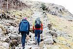Young couple hiking, rear view, Honister Slate Mine, Keswick, Lake District, Cumbria, United Kingdom
