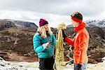 Young couple hiking, holding safety rope, Honister Slate Mine, Keswick, Lake District, Cumbria, United Kingdom