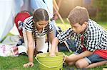 Boy and sister preparing bucket for campfire in garden