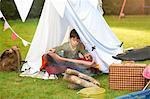 Boy shaking blanket from homemade tent in garden