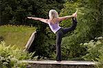 Mature woman practicing yoga dancer pose in garden
