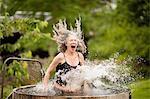 Mature woman splashing into fresh cold water tub at eco retreat