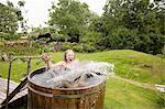 Mature woman jumping into fresh cold water tub at eco retreat