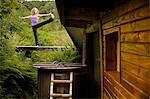 Mature woman practicing yoga pose on footbridge at eco lodge
