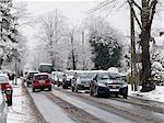 Snowfall hits commuter traffic on suburban road