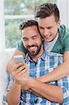Homosexual couple men looking at smartphone