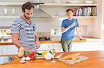 Handsome man cutting vegetables in the kitchen with boyfriend behind