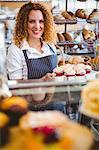 Pretty barista preparing plate with cupcakes
