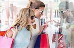 Beautiful women holding shopping bags looking at window