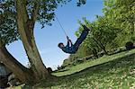 Boy playing on tree swing in backyard