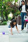 Mother watching daughter draw on sidewalk