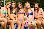 Five teenage girls sitting on a picnic table in bikinis