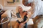 Senior man assisting wife at home