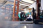 Mechanics working near forklift in auto repair shop