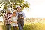 Grandparent farmers and grandson walking along rural wheat field
