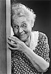 1950s SMILING ELDERLY WOMAN PEEKING AROUND DOOR EAVESDROPPING