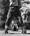 1950s GIRL FALLEN SITTING SIDEWALK WEAR METAL ROLLER SKATES SHOT THROUGH LEGS OF BOY ROLLED CUFF BLUE JEANS