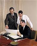 1960s THREE EXECUTIVE MEN MEETING DISCUSSING PAPERWORK PLANS