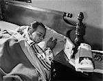 1950s MIDDLE AGED MAN SLEEPING ASLEEP STRIPED PAJAMAS CLUTCHING A PILLOW NIGHT TABLE ALARM CLOCK MAGAZINE