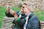 Happy senior women taking selfie through smart phone at park