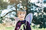 Happy boy in fairy wings looking away at yard