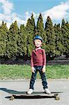 Full length portrait of happy boy standing on skateboard against trees