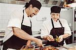 Smiling chefs garnishing dish in kitchen