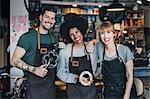 Portrait of happy multi-ethnic mechanics with gears in workshop