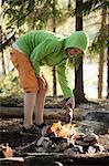Boy igniting campfire at lakeshore