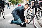 Businessman looking away while repairing bicycle on street