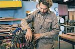 Carpenter arranging tools in belt at workshop