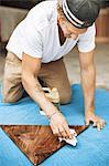 Carpenter polishing triangle shaped wood at workshop