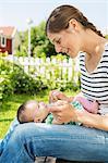 Smiling woman looking at baby while sitting at yard