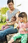 Woman with baby looking at girl eating banana outdoors
