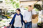 Happy senior couple walking at flower market
