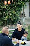 Happy family having dinner at table in yard