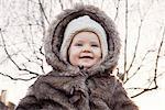 Baby girl wearing fur coat outdoors, portrait