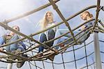 Three friends sitting on climbing net in playground, Munich, Bavaria, Germany