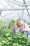 Mature woman admiring Hydrangea flower in garden centre, Augsburg, Bavaria, Germany