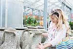 Mature woman choosing urn in greenhouse, Augsburg, Bavaria, Germany