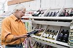 Customer reading label on bottle in supermarket, Augsburg, Bavaria, Germany