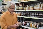 Customer reading label on a schnapps bottle in supermarket, Augsburg, Bavaria, Germany