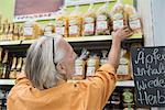 Customer in supermarket choosing noodles packet, Augsburg, Bavaria, Germany
